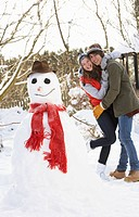 Teenage Couple Building Snowman
