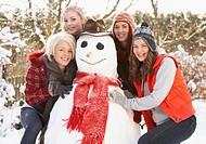 Group Of Teenage Girls Building Snowman