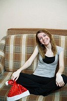pretty girl in the Christmas hat on sofa smiling