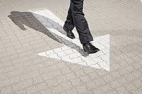 detail of business person walking on pavement with arrow