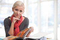 portrait of young blonde businesswoman reading file