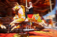 Young girl riding the Carousel funfair ride at Cardiff bay, south Wales