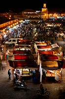 Overview of crowds at food booths and shops at night in Place Djemaa el Fna square Marrakech Morocco