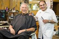 Barber cutting customer´s hair in barbershop
