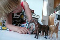 Young Blonde Girl Playing With Toy Horses