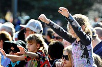Young girl raises hands and arms in crowd during Gasparilla Pirate Festival Parade Tampa Florida