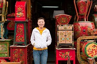 Saleswoman in her furniture shop, Panjiayuan flea market, Chaoyang District, Beijing, China, Asia