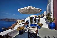 Cliffside view from deck with umbrella in the village of Oia in Santorini, Greece