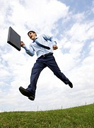 Handsome businessman with briefcase in hand leaping over green grass with cloudy sky at background
