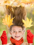 Portrait of laughing young girl holding two maple leaves