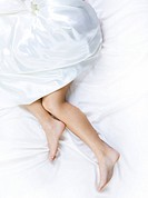 Image of barefooted female legs pointing out of white silk blanket