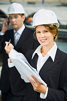 Businesswomen is holding architectural plan and pen on the background of her co_worker