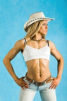 Portrait of cowgirl in hat and white tanktop looking aside over blue background