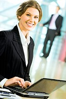 Portrait of smiling businesswoman sitting in the office and typing on the laptop at the background of standing businessman