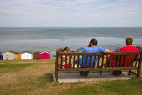 Family on a bench overlooking beach huts and sea at Tankerton near Whitstable, Kent, England, United Kingdom, Europe