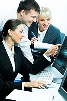 Photo of three smiling students sitting at the desk before the computer looking at its monitor while a girl writing something down