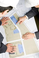 Close_up of engineers looking at blueprints with sketches of projects