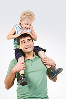 Photo of little boy sitting on fathers neck looking at his eyes