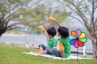 Two boys playing and blowing bubbles