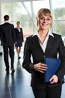 Smiling Caucasian businesswoman in eyeglasses with blue paper case in her hands and two walking businesspeople on the background