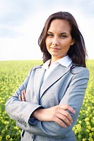 Portrait of young business lady with folded arms in flower field