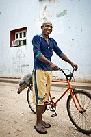 Man carrying a pork on his bicycle for new year's eve, Baracoa, Guantanamo, Cuba, Caribbean