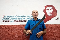 Peasant with a machete in front of a painting with a Che's phrase  Holguin, Cuba, Caribbean