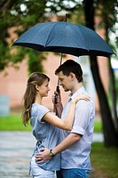 Portrait of couple in love standing outside under umbrella and looking at each other
