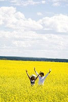 Photo of joyful couple raising their hands while standing in flowery meadow at summer