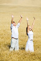 View of happy people raising their hands standing in the field