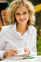 Pretty smiling businesswoman with the cup of coffee outdoor