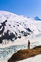 Male hiker overlooks Exit Glacier and the Harding Icefield from a ledge on Harding Icefield Trail, Kenai Fjords National Park, Kenai Peninsula, Southc...