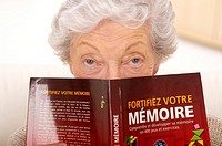 senior woman with a book on how to exercise memory