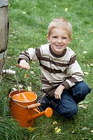 Boy filling watering can