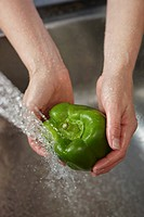 Woman washing green pepper