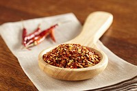 Wooden spoon containing dried hot pepper flakes