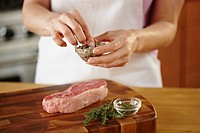Woman seasoning raw steak with frresh herbs