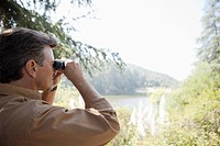 Man outdoors with binoculars (thumbnail)
