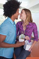 Young couple eating take out noodles