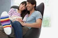 Young couple watching a movie at home