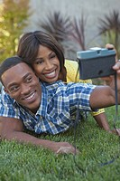 Young couple lying on a lawn taking photos