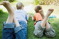 Boys relaxing near pond