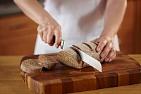 Woman slicing a loaf of bread