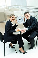 Portrait of two businesspeople sitting at table in the office and holding clock showing that its time for coffee break
