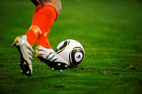 Legs of a football player with Jabulani, the official match_ball of the FIFA Football World Cup 2010 in South Africa