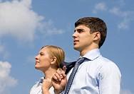 Portrait of confident business partners looking forward against blue sky