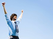 Portrait of happy businessman lifting up hands on the background the sky