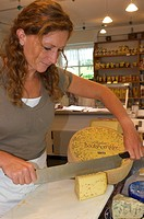Saleswoman cutting Bockshornkleekaese, Fenugreek cheese, in the Kaeskueche cheese dairy in Isny, Allgaeu, Bavaria, Germany, Europe