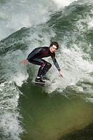 Teenage boy surfing in Eisbach, Munich, Bavaria, Germany