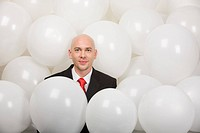 Man surrounded by balloons at corporative party